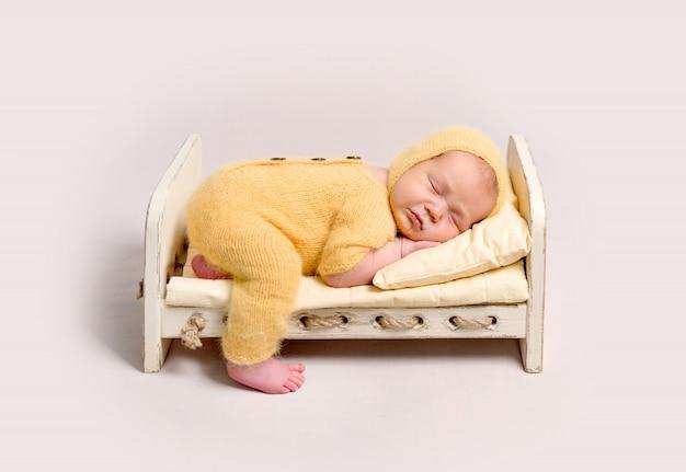 Bebê vestido com traje de malha amarelo dormindo no berço