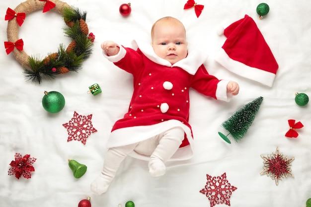 Bebê vestido para o primeiro natal com decoração de natal em fundo branco.