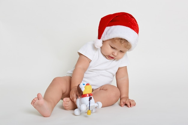Bebê vestindo macacão e chapéu de natal brincando com o novo brinquedo branco sentado descalço isolado no espaço em branco