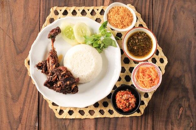 Bebek madura, menu tradicional de pato frito em indonésio. menu popular veio de madura, east java. normalmente servido com vegetais crus e sambal picante. popular como penyetan