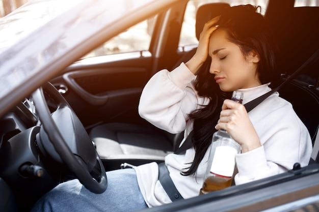 Bebendo ao volante. uma mulher bêbada dirige um carro.