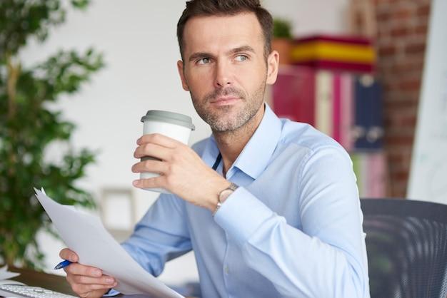 Bebendo café e desviando o olhar dos documentos