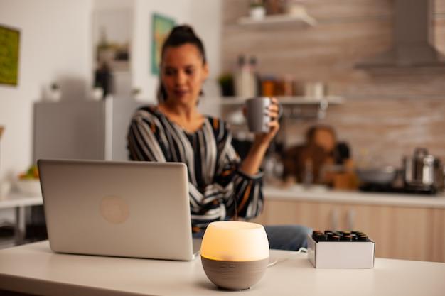 Bebendo café e trabalhando com aromaterapia com óleos essenciais de difusor