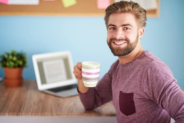 Bebendo café e trabalhando no laptop