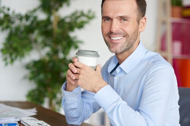 Bebendo café sorrindo enquanto faz uma pausa