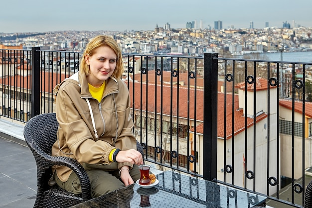 Bebendo chá em frente à paisagem urbana de istambul, jovem branca se senta à mesa no telhado do hotel.