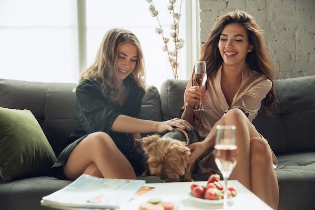 Bebendo champanhe, amigas garotas brancas curtindo uma festa de despedida de solteiro no fim de semana