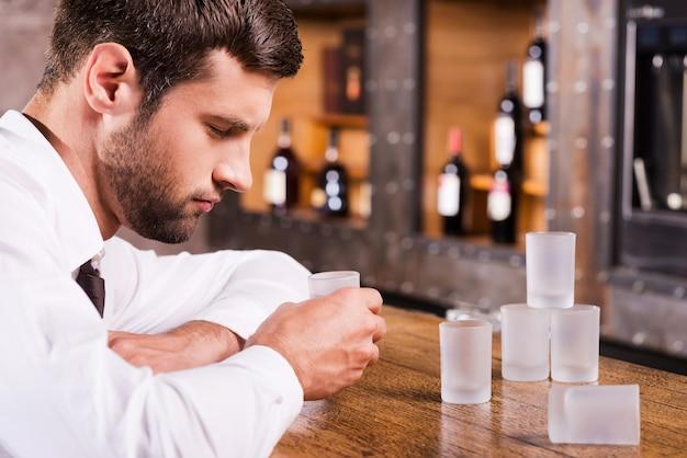 Bebendo novamente. homem deprimido e bêbado de camisa e gravata encostado no balcão do bar e dormindo com os copos vazios em pé perto dele