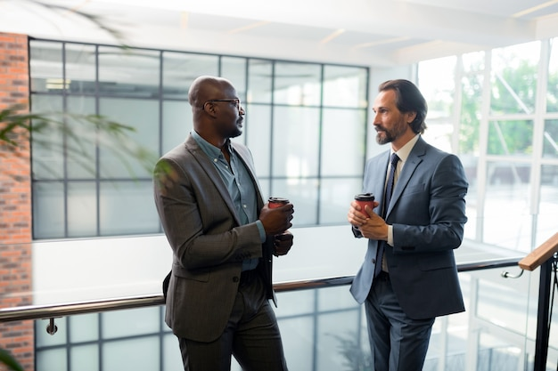 Beber café. dois empresários conversando e tomando café pela manhã antes da negociação