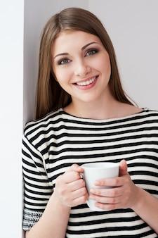 Beber café fresco. mulher jovem e bonita com roupas listradas, encostada na parede e segurando a xícara