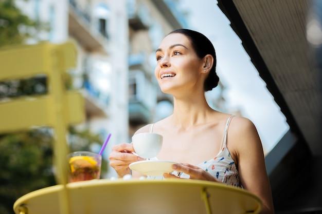 Beber café. mulher jovem e emocional alegre sentada com uma xícara de café ao ar livre e sorrindo