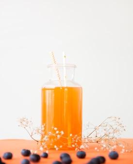 Beber canudo no pote de uma garrafa de suco de laranja com galho gypsophila e mirtilos contra o pano de fundo branco