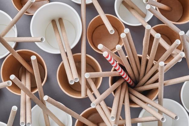 Beber canudos de tubos marrons feitos de papel e amido de milho em copos de café de papel vazios em um fundo cinza da moda. resíduos zero e conceito livre de plástico. vista do topo.