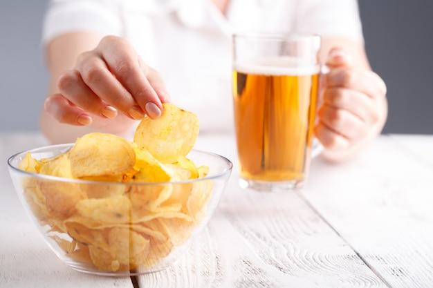 Beber cerveja e comer junk food, feminino em casa à noite
