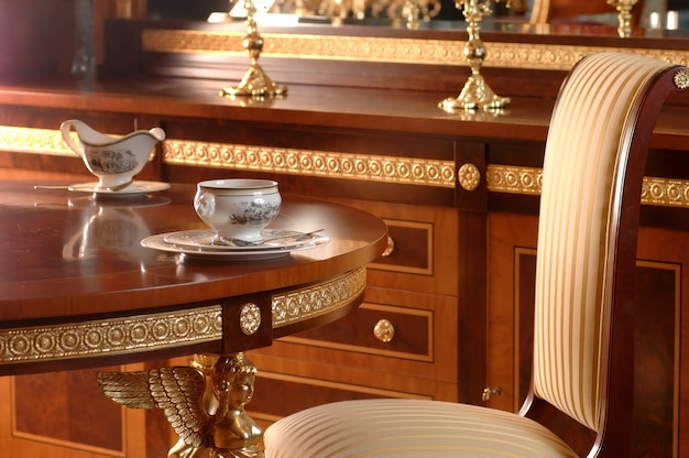 Beber chá à mesa na poltrona e móveis de madeira