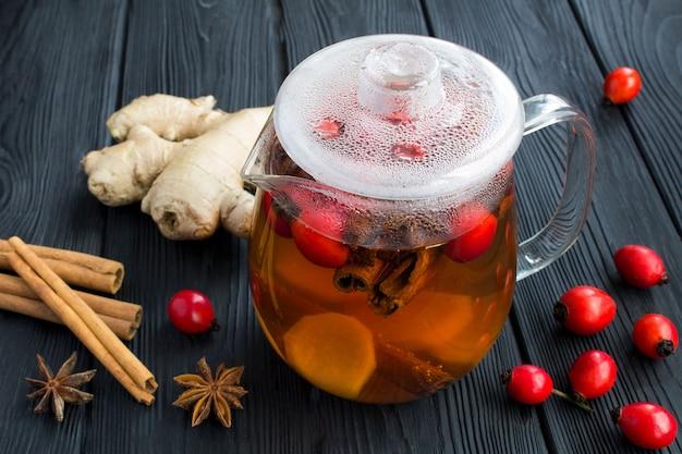 Beber chá com rosa canina, gengibre e especiarias no bule de vidro