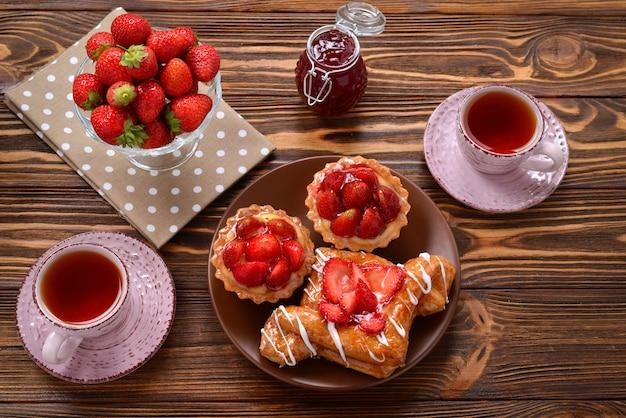 Beber chá com tortinhas e bolos com morangos