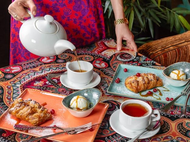Beber chá, o chá é servido em uma bela mesa com strudel fresco de dar água na boca. vista lateral
