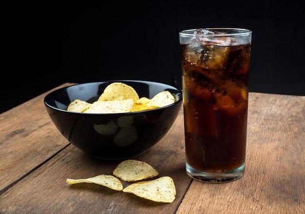 Beber coca-cola com gelo no copo na mesa de madeira velha