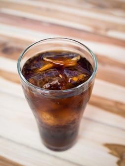 Beber coca-cola com gelo no copo na mesa de madeira