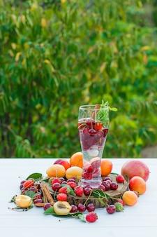 Beber com frutas, especiarias, tábua em um copo com fundo de madeira e jardim, vista lateral.