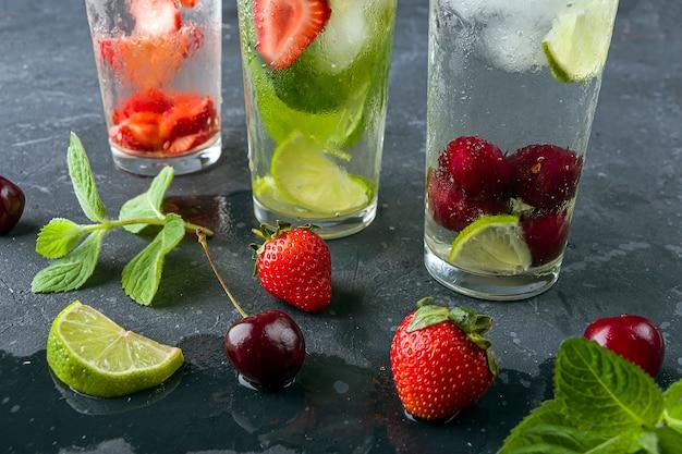 Beber com morango e limão cereja e hortelã em fundo escuro. coquetéis de mojito