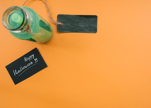 Beber em garrafa com rótulo ao lado de inscrição com felicitações alloween em fundo laranja