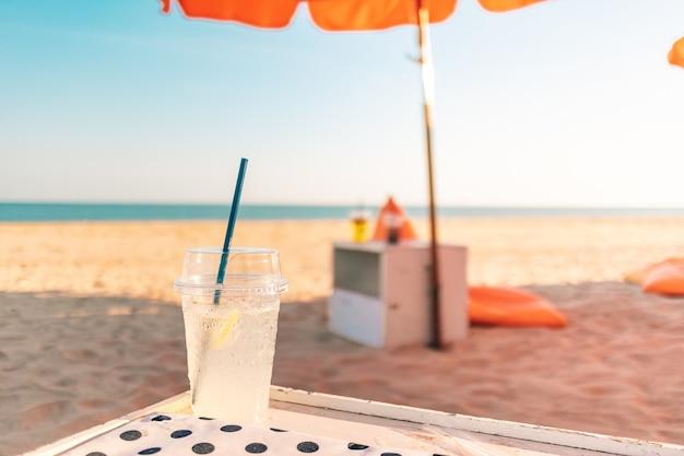 Beber refrigerante fresco na praia no verão.