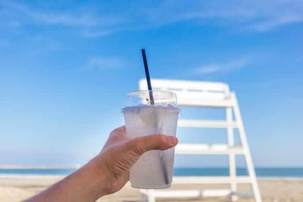 Beber refrigerante fresco na praia no verão