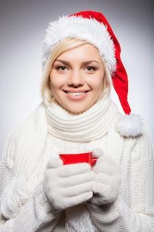 Beber uma bebida quente no natal. mulher jovem e bonita com chapéu de papai noel segurando uma xícara vermelha e sorrindo enquanto isolada em cinza