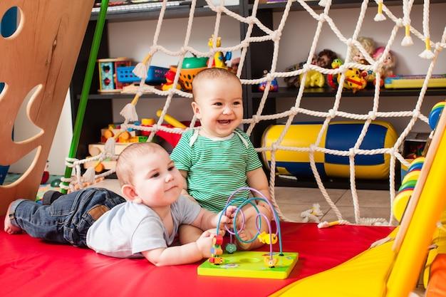 Bebês de dois meninos espertos brincando com um brinquedo na sala de jogos