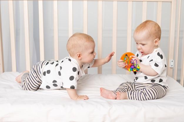 Bebês gêmeos brincam no berço, desenvolvimento inicial de crianças de até um ano