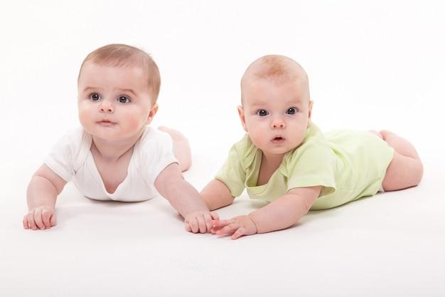Bebês menina e menino deitado de mãos dadas