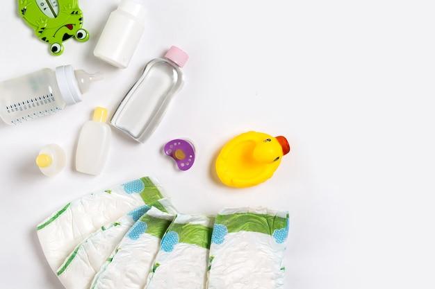 Bebês mercadorias fralda bebê pó creme shampoo óleo sobre fundo branco com cópia espaço vista superior ou fl ...