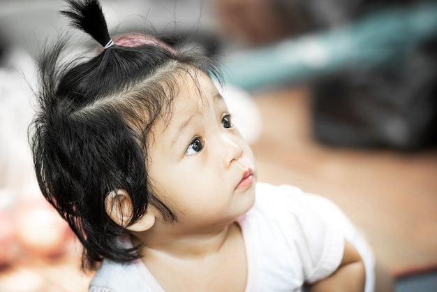 Bebezinha asiática olhando para algo