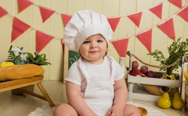 Bebezinha feliz com boné branco e avental sentada na cozinha