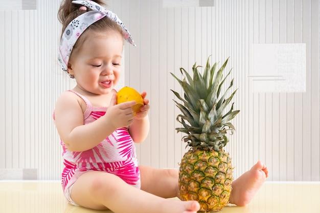 Bebezinha fofa com camisa rosa com estampa tropical sentada na mesa comendo limão