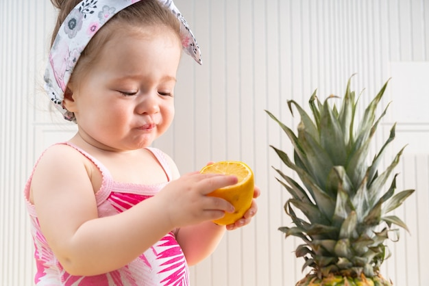 Bebezinha fofa enrugando o rosto ao brincar com metade de um limão