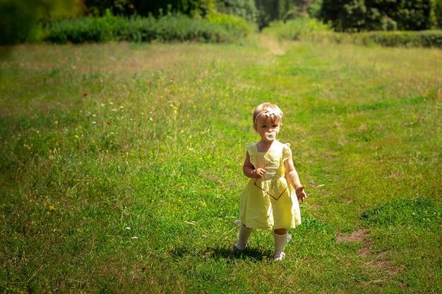 Bebezinha fofa num vestido amarelo, olhando para a câmera no jardim verde