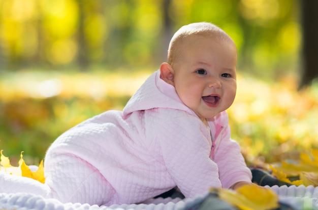 Bebezinha gordinha e fofa rindo da câmera enquanto engatinha em um tapete na grama em um parque de outono