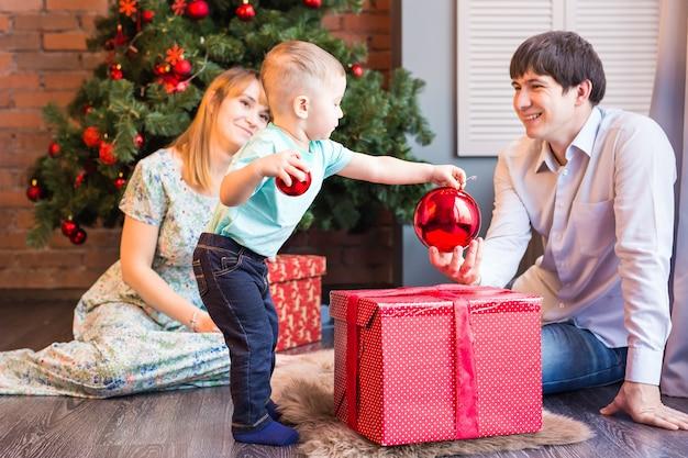 Bebezinho a decorar uma árvore de natal, brinquedos. feriados, presente e conceito de ano novo.