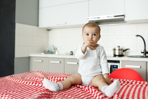 Bebezinho adorável sentado na mesa da cozinha