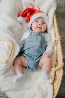 Bebezinho alegre de pijama azul deitado na colcha branca