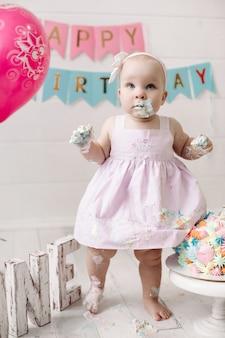 Bebezinho bonitinho com vestido rosa sujar-se no creme de bolo, comemorando o feriado completo. feliz aniversário de criança feminina engraçada posando em um interior moderno e festivo