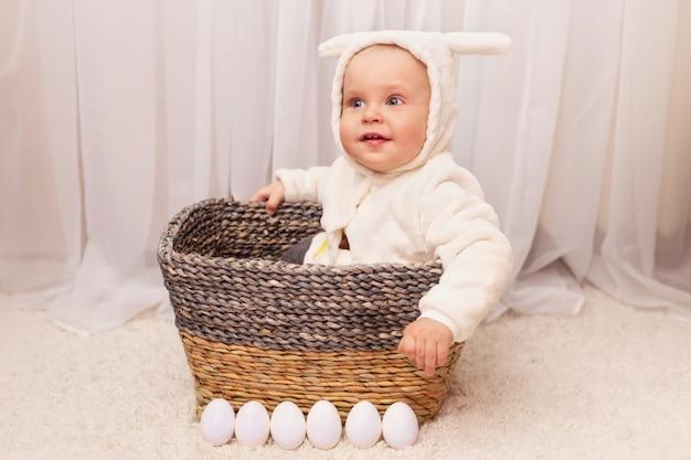 Bebezinho bonitinho na fantasia de páscoa coelho sentado na cesta com ovos em casa