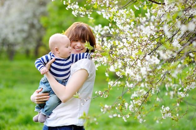 Bebezinho com a jovem mãe no jardim de flor