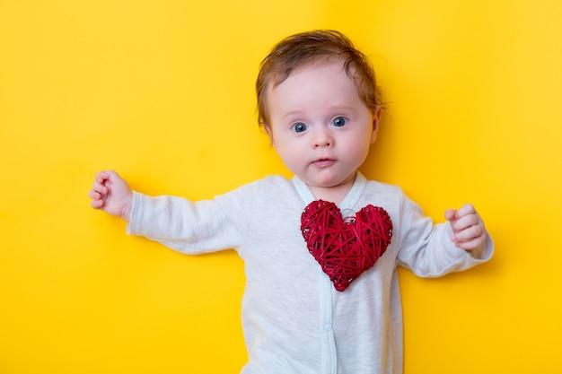 Bebezinho com brinquedo em forma de coração vermelho