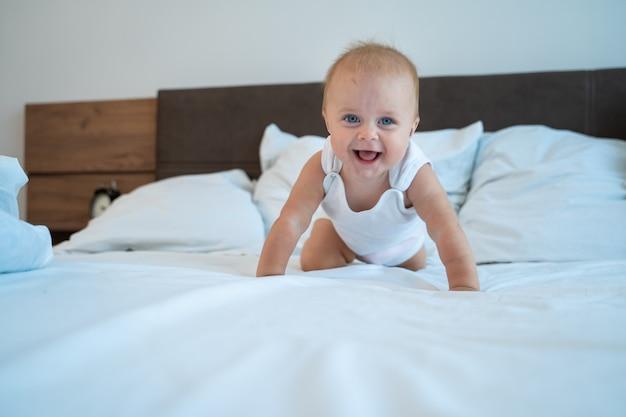 Bebezinho com grandes olhos azuis na cama no quarto de casa