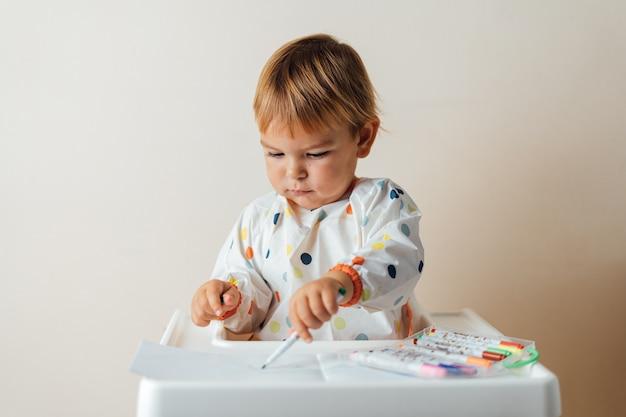 Bebezinho da criança brinca com canetas de ponta de feltro, desenhando linhas coloridas em papel