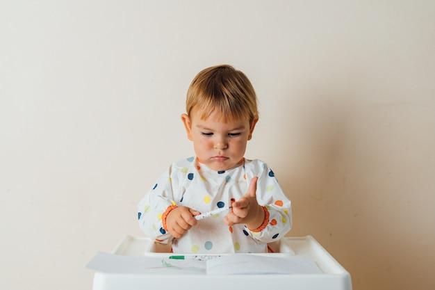 Bebezinho da criança brinca com canetas de ponta de feltro, desenhando linhas coloridas em si mesma